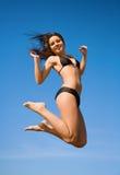 比基尼泳装高跳的妇女 免版税图库摄影