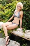 比基尼泳装loge坐的妇女 免版税图库摄影