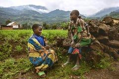 比温巴,卢旺达- 2015年9月9日:未认出的孩子 穿传统衣裳的孩子坐草 免版税库存照片