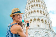 比萨斜塔微笑的妇女旅游采取的照片  免版税库存照片