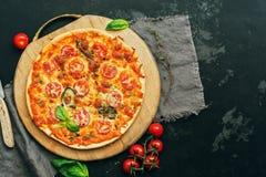 比萨玛格丽塔用西红柿、无盐干酪和蓬蒿在一个切板 顶视图,平的位置 被定调子的照片 库存图片