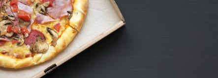 比萨用烟肉、蕃茄、蒜味咸腊肠、乳酪和蘑菇在一个纸板箱在黑暗的桌上 从上,平的位置 文本的空间 免版税库存照片