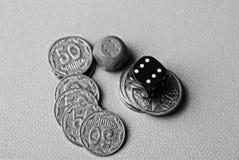 比赛块和硬币在一张灰色桌上 免版税库存照片