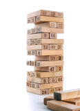 比赛jenga块在白色背景的 垂直的塔整个和在比赛 在堆的木块与图数字 图库摄影