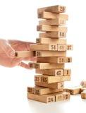 比赛jenga块在白色背景的 垂直的塔整个和在比赛 在堆的木块与图数字 库存图片