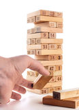 比赛jenga块在白色背景的 垂直的塔整个和在比赛 在堆的木块与图数字 免版税库存照片