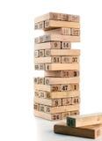 比赛jenga块在白色背景的 垂直的塔整个和在比赛 在堆的木块与图数字 库存照片