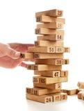 比赛jenga块在白色背景的 垂直的塔整个和在比赛 在堆的木块与图数字 免版税图库摄影