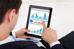 比较在数字式片剂的商人图表在办公室 免版税图库摄影