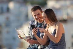 比较智能手机和地图的结合游人在镇 免版税图库摄影