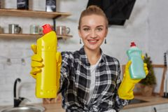 比较洗涤剂产品的妇女,她拿着两个瓶并且在家检查他们厨房 免版税库存照片
