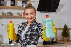 比较洗涤剂产品的妇女,她拿着两个瓶并且在家检查他们厨房 免版税图库摄影