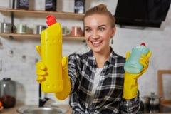 比较洗涤剂产品的妇女,她拿着两个瓶并且在家检查他们厨房 免版税库存图片