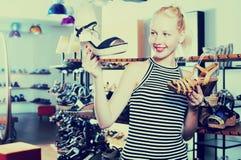 比较鞋子的女孩在商店 库存照片