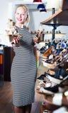 比较鞋子的女孩在商店 免版税图库摄影