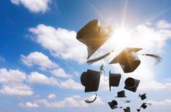 毕业典礼,毕业盖帽,在天空中投掷的帽子与 免版税库存照片