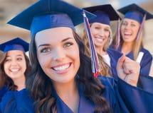 毕业在方帽与长袍的小组青少年的女孩在校园里 库存图片