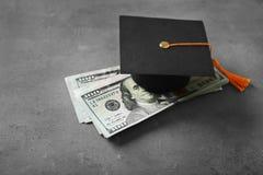 毕业在桌上的帽子和美元钞票 免版税库存图片