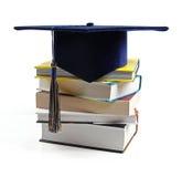 毕业在白色隔绝的帽子和堆书 免版税库存照片