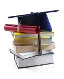 毕业帽子和文凭在堆书 免版税库存照片