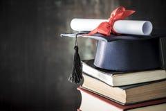 毕业帽子和文凭在桌上 图库摄影