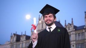 毕业成套装备的人微笑和显示文凭的对照相机 股票录像