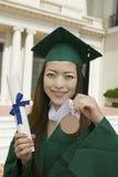 毕业生举行的文凭和奖牌大学外 库存图片