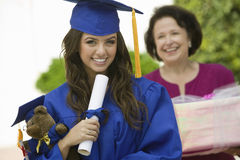 毕业生举行的玩具熊和文凭外面 免版税库存图片
