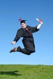 毕业生喜悦跳的男 免版税库存照片