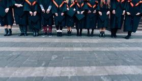 毕业生在手上的拿着他们的帽子 戴长袍和帽子在他们的手上的毕业生 小组学士褂子的学生 库存照片