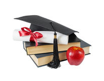 毕业生帽子、书、苹果和纸卷 免版税库存照片