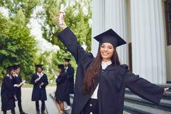 毕业生年轻西班牙女性毕业生背景大学的 免版税库存图片