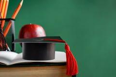 毕业生盖帽和苹果在旧书在图书馆绿化墙壁backgro 图库摄影