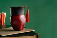 毕业生盖帽和苹果在旧书在图书馆绿化墙壁backgro 免版税库存图片