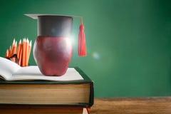 毕业生盖帽和苹果在旧书在图书馆绿化墙壁backgro 免版税图库摄影