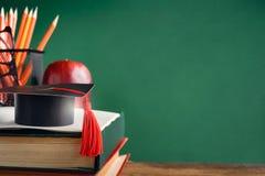 毕业生盖帽和苹果在旧书在图书馆绿化墙壁backgro 库存照片