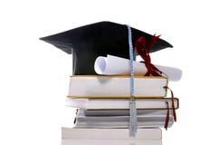 毕业盖帽、书和滚动 免版税库存图片