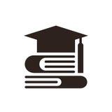 毕业盖帽和书。教育标志 免版税库存图片