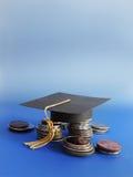 毕业盖帽和硬币 免版税库存图片