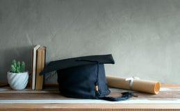毕业盖帽,有程度纸的帽子在木桌毕业c 免版税库存图片