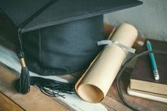 毕业盖帽,有程度纸的帽子在木桌毕业c 免版税库存照片