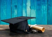 毕业盖帽,有程度纸的帽子在木桌,葡萄酒上求爱 库存图片