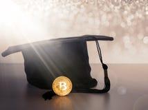 毕业盖帽,有金黄bitcoin硬币的帽子 库存图片