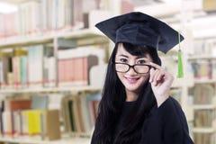 毕业褂子姿势的亚洲人毕业生在图书馆 免版税图库摄影