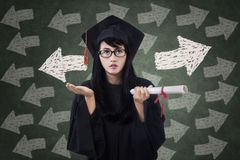 毕业褂子的迷茫的女学生 免版税库存照片