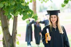 毕业:站立与与后边朋友的文凭的学生 图库摄影