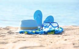 毛巾、帽子、触发器和风镜在沙子在海附近 海滩对象 库存图片