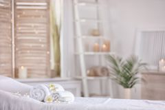 毛巾和蜡烛在按摩桌上在现代温泉沙龙 安置放松 图库摄影