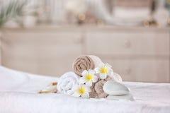 毛巾和蜡烛在按摩桌上在现代温泉沙龙 安置放松 库存照片