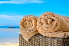 毛巾在藤茎桌滚动了在海滩 免版税库存照片